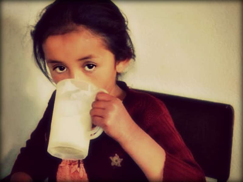 A young Guatemalan girl drinks what is most likely her only meal of the day, a glass of porridge. Photos by Mandi Burgess